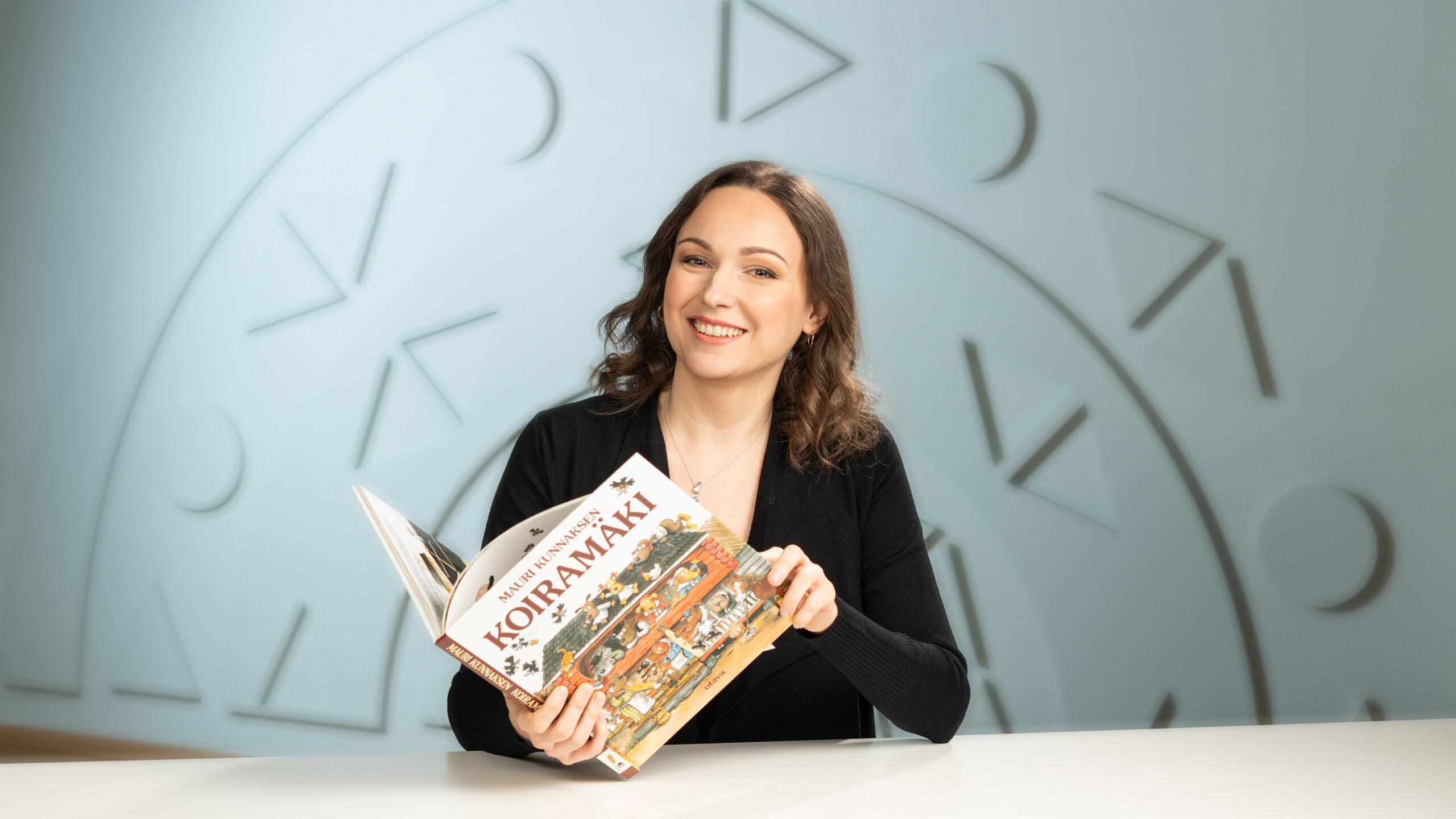 Naine istub laua taga, raamat käes