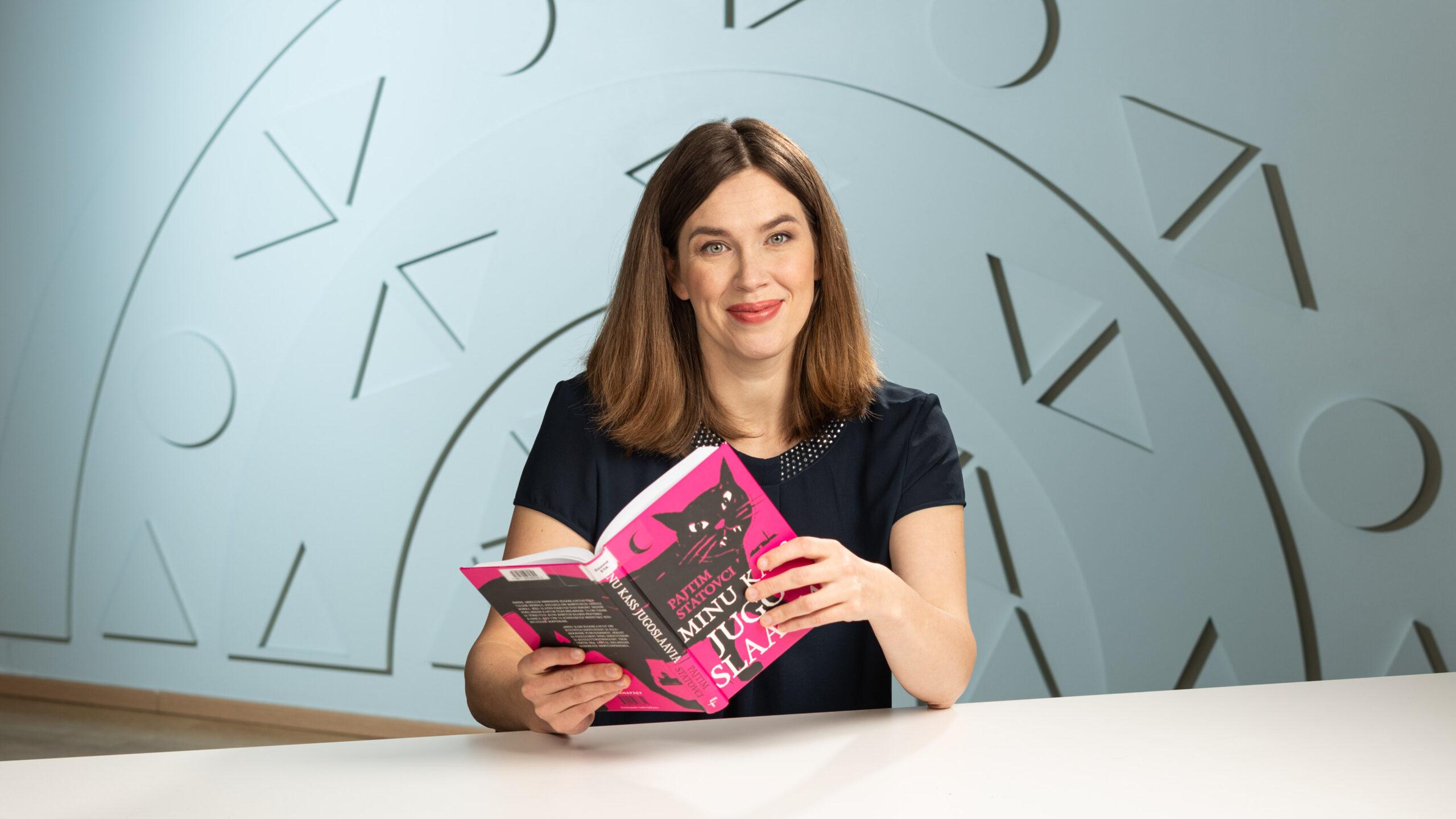 Naine istub ja poseerib raamatuga