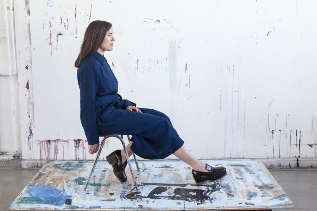 mantlis naine istub toolil